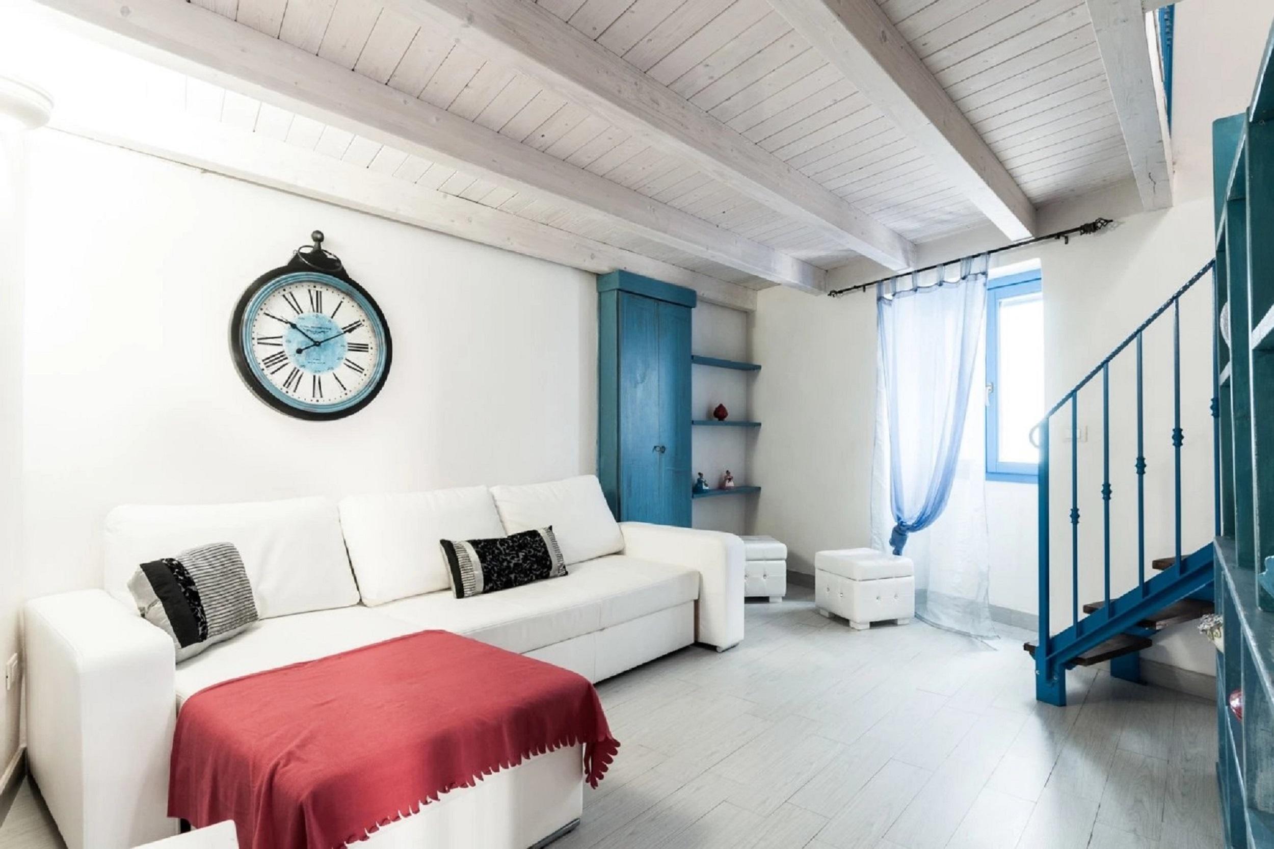 salotto con divano bianco e coperta rossa, scale con ringhiera blu