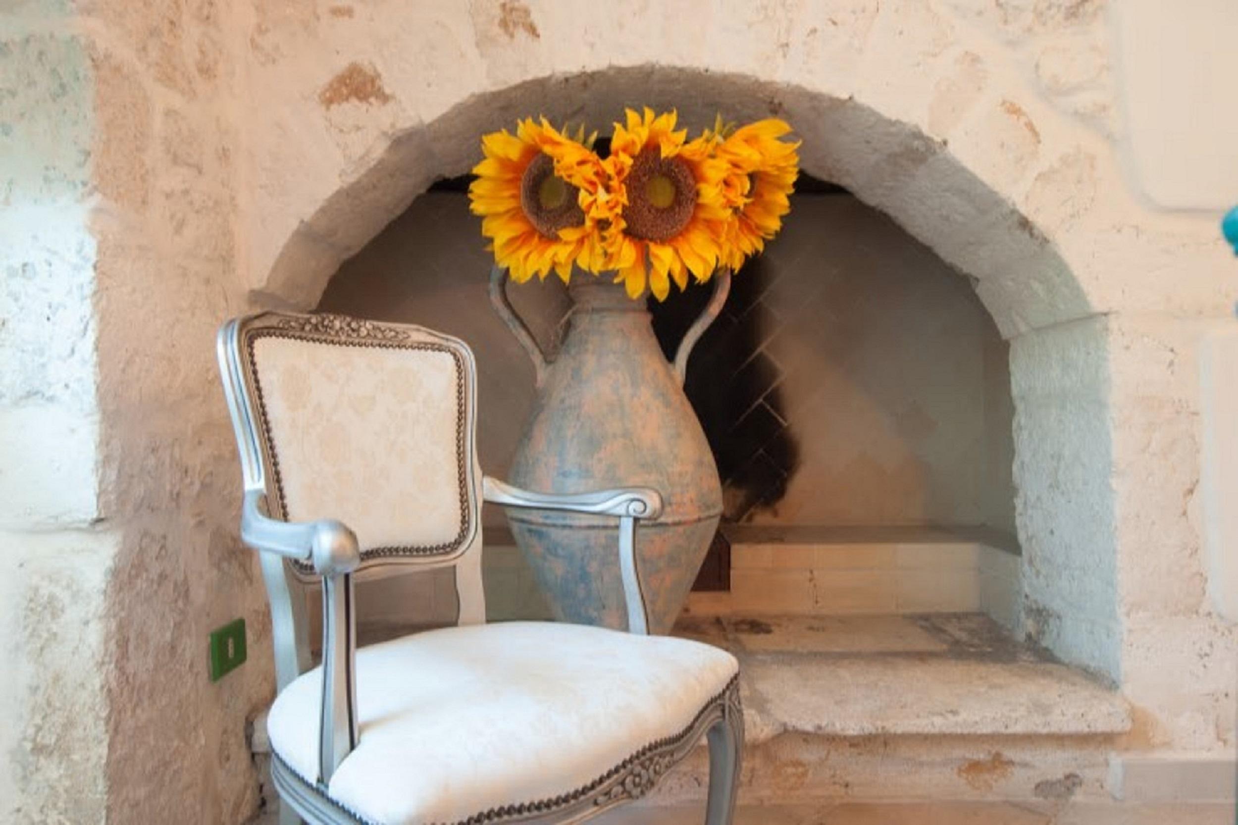 sedia bianca e sullo sfondo vaso con girasoli in una casa tipica in Puglia