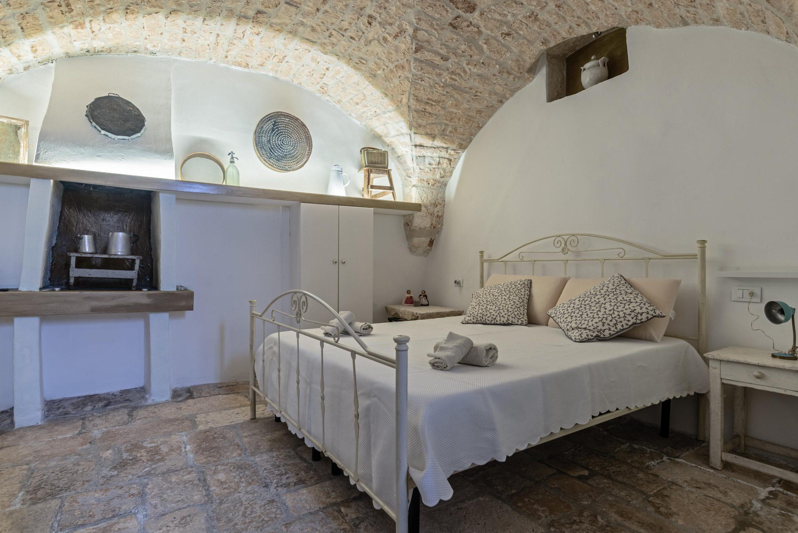 camera con letto matrimoniale bianco in una casa tipica pugliese