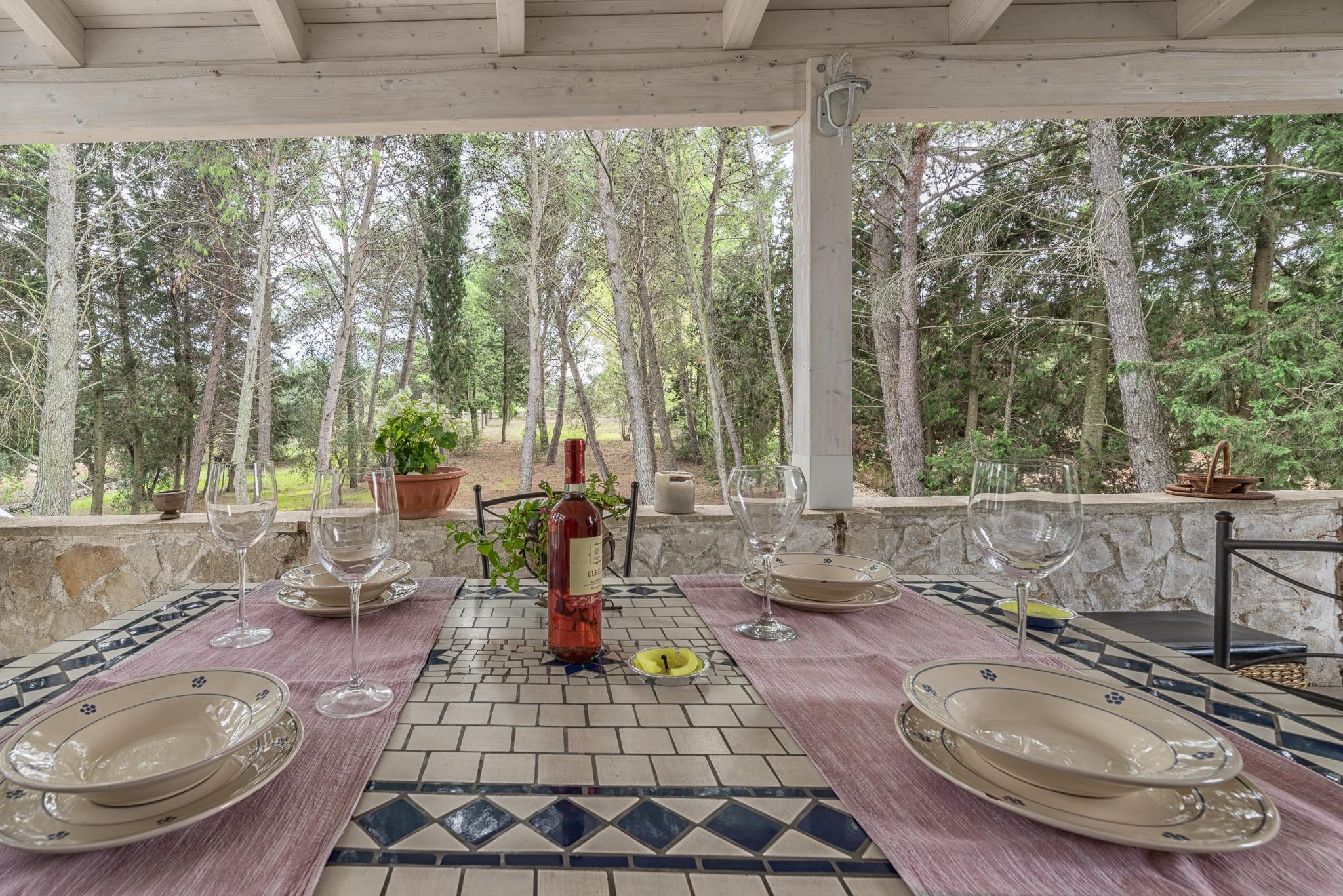 tavolo apparecchiato sotto portico con vista giardino